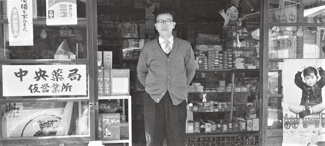 モノクロ写真。店舗前に社長が立っている