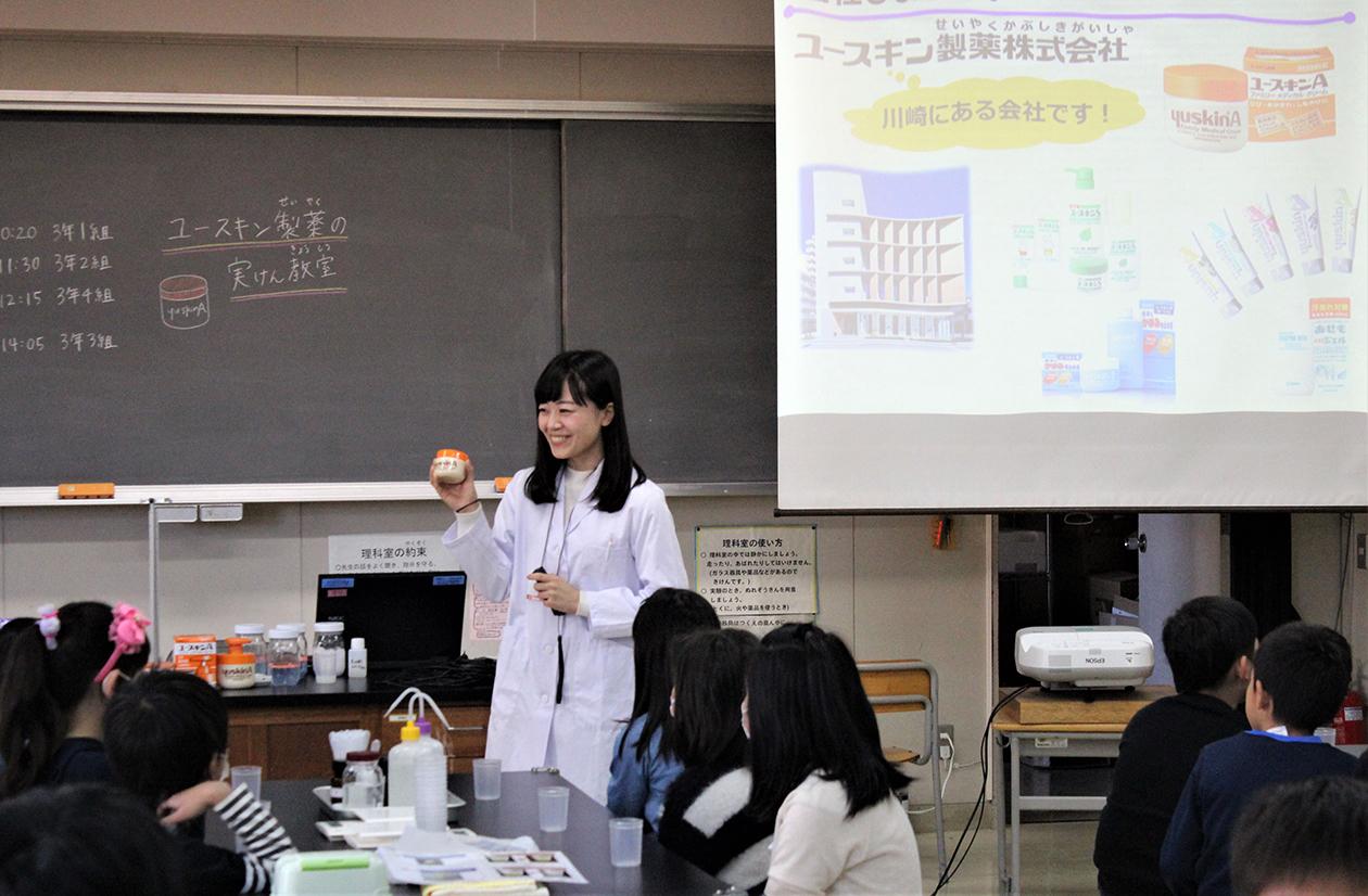 白衣を着た社員が教室で子どもたちに向けて授業をしている