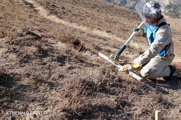 荒野で防具服を身に着けた男性が地雷探査機を使い地雷の除去活動を行っている