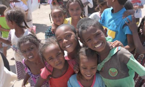 スーダンに暮らす子どもたちが肩を組んで笑顔で楽しそうにしている