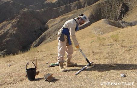 荒野で防護服を着た男性が地雷探査機を地面にかざしている